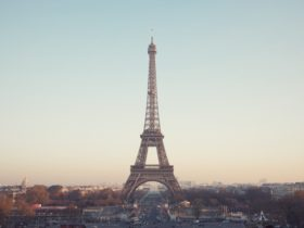 a shot of the eiffel tower from a good distance away shows it with a hazy, multicolored sky