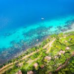 an aerial view of a beach on phu quoc island shows turquoise and blue ocean with lush green vegetation on land