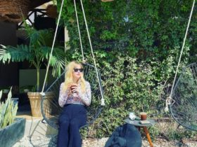 mary blackiston sits on a swing looking left while holding a coffee in both hands